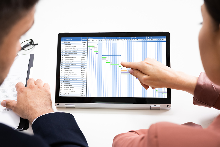 Two worker looking at a timesheet app in Australia displayed in a monitor